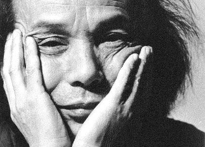 Headshot of Toru Takemitsu with hands holding face