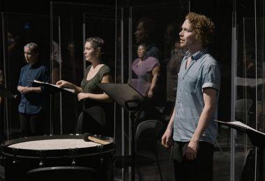 Performers behind plexiglass